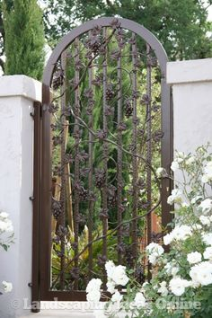 A custom wrought iron gate allows light and air to circulate while still providing privacy and adding a touch of elegance.