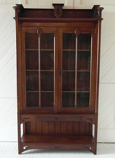 Arts & Crafts glazed two door bookcase with capped columns, pierced and carved detail.  Circa 1905