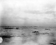 Omaha Beach, à mer haute, la mer est agitée sans être démontée. Des GI's sont accrochés sur des épaves.  On peut noter les éléments suivants : En arrière plan le croiseur USS Augusta (CA-31) navire amiral de la Western Naval Task Force TF 122 du Rear Admiral Alan G. Kirk avec à son bord le général Bradley, en position devant Fox à Omaha,
