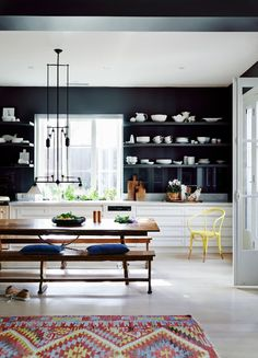 Kitchen with dark walls, farm table, and casual kilim add up to relaxed dining with style in Oct 23 1014 Dpages on casual dining.