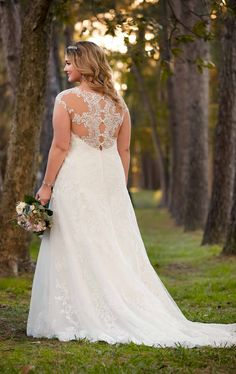 This plus size romantic A-line wedding gown from Stella York boasts eye-catching lace cap sleeves and a scalloped-lace illusion back with pretty fabric-covered buttons. The sweetheart neckline frames the face and features a scalloped lace trim that coordinates with scalloped lace on the hem. The lower back zips up with ease. This romantic scalloped-lace wedding dress is available in plus sizes.