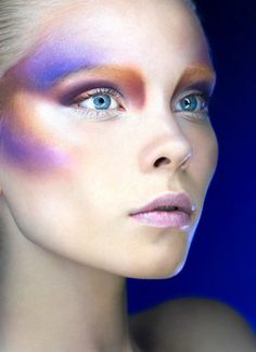 Signal blue and lilac shadow on cheeks and above eyebrow, red orange tinge over cheek and under eyebrows & corners of eyes, lilac pink lips, blue eyes, white-blonde hair.