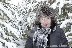 A woman of mature years in a fur hat between young pine trees covered with snow