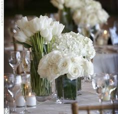 Simple white flower centerpieces minimalist pinterest white alternating high and low centerpieces of white tulips white hydrangeas and white roses mightylinksfo