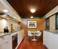 juxtaposition of high gloss white cabinets with warmth of wood wall, stunning orange floor, dark ceiling and unobtrusive pendant, fabulous small corner nook with tulip table and Eames chairs, is that even Inuit art on the wall?  masterful