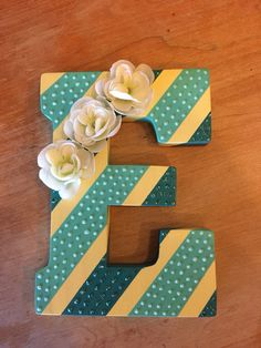 DIY wall art. Painted wooden letter with stripes. Glitter and flowers added for embellishment.   Wooden letter E (Hobby Lobby) Paint- Lemon ice and Aqua (Joann Fabrics brand), Laguna (Apple Barrel brand) Glitter- Stickles colors Aqua and Crystal Flowers (Hobby Lobby)