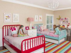 Girl's Bedroom: Bright Beds and Rainbow Rug - Love the Spindle beds with the trundles under them!!! Perfect for Lily and Soph!