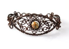 """It's a little bit of my love for paisley combined for my appreciation of Art Nouveau. All Bohemian. This artisan, wire wrapped, filigree bracelet is woven from pure copper and features a 8 mm, Crazy Lace Agate gemstone accented by 4 mm agate gemstones. The large, center shape is filled with intricate, copper swirls. The entire piece has been oxidized for an antique finish and then polished for luster.     The bracelet shown in the image is a """"prototype.""""  Your bracelet will be made just for…"""