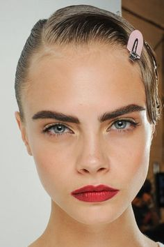 Cara Delevingne pays homage to this season's hottest make-up trends. Dewy skin and a statement red lip = recipe for fashion glory!