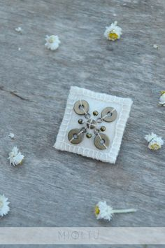 White woolen textile brooch. Brooch with  brass beads. Simple
