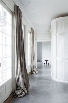 Extra-long hanging linen curtains add a softness to a minimal interior. The off-grey color also make these window treatments feel light and full of movement.