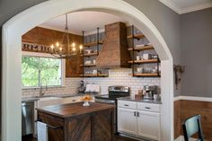 Chip and Joanna cut a wide archway to open up the kitchen and dining room, letting light flow throughout the space. They also created industrial-style open shelves made from plumbing pipes and reclaimed wood.