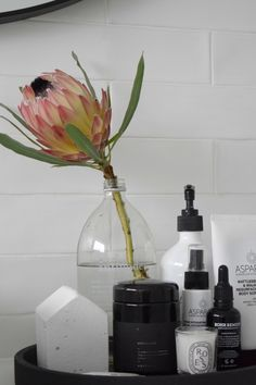 Black and white bathroom styling with King Protea flower in an antipodes bottle. Features black concrete  Zakkia tray, white Zakkia concrete house, ASPAR spa products, and black Nocturna candle.