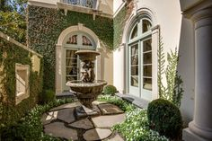Enter through double wood-and-iron doors to an inviting outside front foyer, which overlooks views of a fabulous enclosed outdoor courtyard with elegant landscaping and a stone fountain accented with a Pennsylvania Bluestone surround. The outside foyer leads through double iron-and-glass doors to an exquisite two-story entrance hall I Doris Jacobs Real Estate