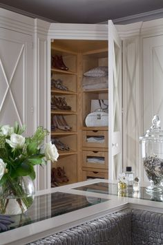 Beautiful walk-in closet features built-in bench upholstered in a gray velvet faux croc fabric framed by an L-shaped closet island with clear glass top placed in front of floor to ceiling built-in cabinets accented with trim moldings. Master Closet, Closet Bedroom, Closet Space, Walk In Closet, Closet Doors, Shoe Closet, Corner Closet, Dressing Room Decor, Dressing Room Closet