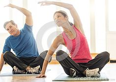 Fit mature couple practicing yoga on mat at home. http://www.dreamstime.com/stock-photo-fit-couple-practicing-yoga-mat-home-full-length-mature-image52146709