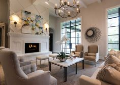 White and beige living room features a high ceiling dotted with white wood beams and a black and gold curvy chandelier illuminating a pair of burlap french wingback chairs facing a pair of linen tufted chairs facing each other across from a stone top coffee table atop a beige diamond woven rug. A pair of white linen stools sit in front of a white brick fireplace and hearth lined with a blue and gold abstract canvas art piece illuminated by iron wall sconces. Elizabeth Garrett Interiors