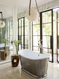 The master suite features his and hers bathrooms with Misses Kayne's half featuring a Waterworks tub and wood stump side table for a little R&R.