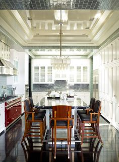 """How do you brighten up a windowless interior kitchen? Gambrel added a skylight. """"I looked for reflective materials—custom-made glass tiles for the walls, glass-fronted cabinets, and beautiful lacquered floors—that would react to that filtered light,"""" he says. """"The space feels fresh and happy, and you can see the clouds passing over when you look up."""""""