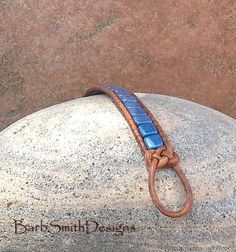 The Skinny One in Knots (Blue Suede) This slender single-wrap beaded cuff bracelet features Blue Suede tile beads stitched on light brown Indian leather cord. The closure is a 3/4 antique silver southwest flower button and single leather loop, accented with Josephine knots on each side. Measure your wrist! This bracelet measures 6 3/4 and fits up to a size 6 1/2 (with a little ease for buttoning). IMPORTANT NOTE ABOUT SIZING: Please measure your wrist with a tape measure. This is a custom…