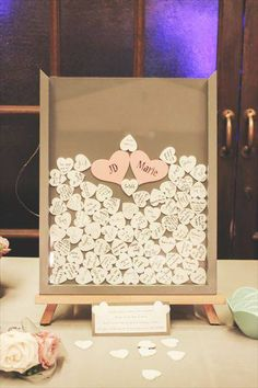 Guests sign their name on a little wooden heart and drop it in a shadow box frame. Way better than a guest book. I love this idea!!
