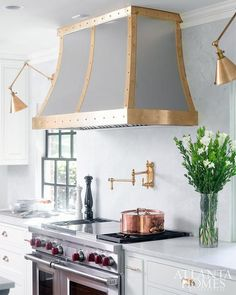 A French steel hood accented with brass studded straps is mounted between Boston Functional Library Wall Lights to a white quartz backsplash above a brass swing arm pot filler fixed above a Wolf range.