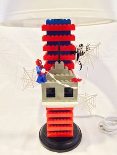 This is a handmade, Spiderman Lego Lamp. Featured on this lamp is Spiderman on a building in a battle against the villain Venom. The wooden
