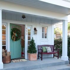 A red-painted bench, copper firewood bucket, and a fir wreath provide a warm holiday welcome.