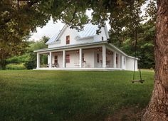Farmhouse with a wrap around porch and a rope swing.