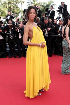 French model and actress Noemie Lenoir wears a bright yellow Chloe dress on the opening day of the 68th annual Cannes Film Festival.