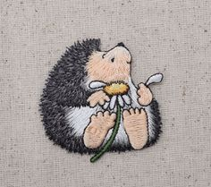 """Hedgehog with Daisy Iron on Applique High quality, detailed embroidery applique. Can be sewn or ironed on. Great for hats, bags, clothing, and more! Size is approx. 2-1/4"""" x 2-1/8"""" or 5.7cm x 5.3cm"""