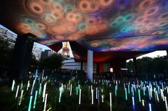 People stand next to an outdoor light installation as they wait to enter the Quai Branly Museum on May 17, 2014, in Paris, during the 2014 European Night of Museums.
