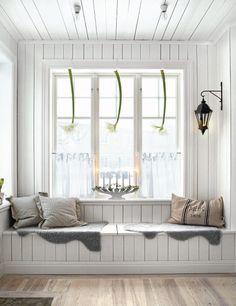 """Observem que interessante esta alternativa: foi construído um baú em madeira com duas tampas sob o peitoril da janela, perfeito para guardar almofadas, edredons e outras roupas de cama que tomam muito espaço no armário e o tampo funciona perfeitamente como um agradável espaço para sentar e ler um livro. Importante que o baú se estenda de parede a parede, para evitar o efeito de """"caixa""""."""