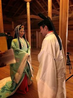 A man and woman dressed in heian robes.