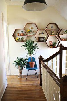 As prateleiras em forma de colmeia são incríveis e deixam a parede ainda mais singela e bonita. Aposte em plantinhas e quadrinhos para enfeitar!