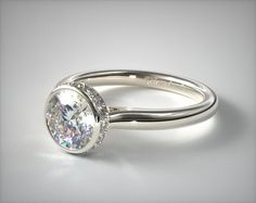 SKU 53324 - The refined elegant feel of a bezel set halo with just a touch of glamour in the pave set diamond crown. Sparkle and fire explodes all around the center diamond of your choice with this breathtaking engagement ring.