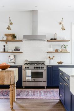 A Beast of a Kitchen Is Now a Blue Beauty - This kitchen is full of colorful painted cabinets and modern decor options. The bar top table and starburst lighting ties the modern kitchen together.   Apartment Therapy