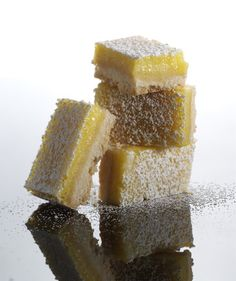 Lemon Bars | A perfect balance of sweet and tart, these lemon bars, prepared in layers, require surprisingly little hands-on work. You'll mix the buttery, shortbread crust and as that bakes, you'll whisk together the creamy, citrus filling. When the crust's baked through, spread the top layer over it, and bake for awhile longer, before letting the whole pan cool in the fridge. One simply but smart shortcut—lining the baking pan with crisscrossed sheets of parchment paper—makes lifting these…