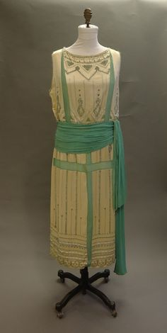 This 1921 French art deco creation is by Jeanne Lanvin. This cream satin dress with an aqua chiffon sash features embroidery and grey beading.