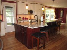 Large kitchen island with plenty of seating, but doesn't interfere with work space. Cream cabinets (Nantucket color, Pioneer design) from Holiday Cabinetry around perimeter, cherry island. Paint color Sherwin Williams Salute. Annapolis Kitchen and Bath.