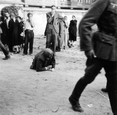 July 1941: An elderly Jewish man, beaten in front of Brygidki prison during the Lviv pogroms, tries to crawl to safety. German soldiers in the foreground pass by him, as Ukrainian civilians in the background cover their faces to shield themselves from the stench of the corpses of prisoners who were killed by members of the Soviet NKVD. German propaganda instigated the pogroms that cost the lives to thousands of Jewish residents.