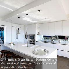Wer eine schöne Küche hat, kann das ruhig ausleben: Mit einem Spiegel zwischen Herdplatte und Hängeschränken entsteht der Eindruck, nebenan befinde sich …