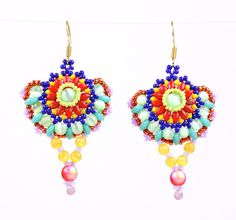 Extraordinary craftsmanship of colorful earrings made to celebrate a loving union or simply brighten your day. A gleaming light green cat's eye glass bead encircled with tiny lime green seed beads to enhance the color, followed by tiers of twin beads, seed beads and cat's eye spheres in dense colors of bold red, sunny yellow, midnight blue, shiny green, sophisticated turquoise and metallic orange edged with tiny picots of lavender seed beads.