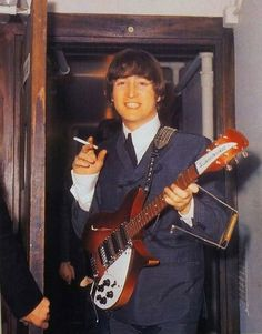 John with his Rickenbacker 325 Rose Morris Fireglo guitar, the 'Beatlebacker', photographed backstage Another Beatles Christmas Show at the Hammersmith Odeon, c. December 1964.