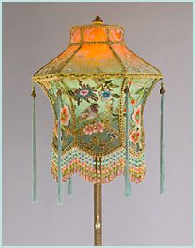 The lantern shaped shade is ombré dyed from orange to celadon to teal and has six panels with an abundance of birds and flowers of vintage hand embroidered appliqués with gold threads.