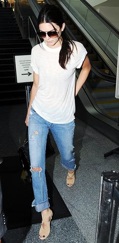 Kendall Jenner wears a white t-shirt, distressed boyfriend jeans, aviator sunglasses, and tan suede heels