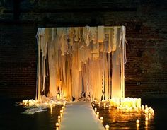 """fabric curls exploded in a sea of candles. That plus the industrial brick background makes for a gorgeous contrast."" Just gorgeous inspiration for places to recreate some day"