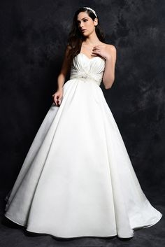 STYLE: GL045          This classic gown is made in Royal Duchess Satin with a strapless sweetheart bodice. The waistline has been defined with a gathered band and encrusted with crystallized beading. This full A-line skirt is made with pleats and a chapel length train. Available in White or Ivory.