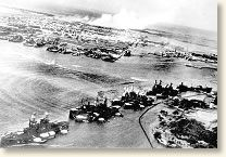 A captured Japanese photo shows Battleship Row under attack. Hickam Field burns in the distance