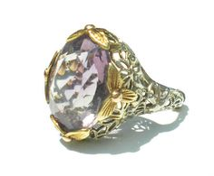 Incredible Art Deco filigree ring set with a faceted amethyst stone. Absolutely gorgeous, has a sizer inside so it will be a larger size if thats removed but currently set to a size 6. No marked but tests positive and guaranteed 14k gold (it might be marked under the sizer). Stone is amethyst, not glass, and is gorgeous. Visit Ribbons Edge for more great pieces of vintage and antique jewelry